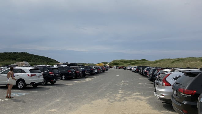 Cars line the parking lot at Cape Cod National Seashore's Head of the Meadow Beach in North Truro on Friday. As of Saturday, the federal parking lot, which last year handled 143,000 visitors, is open only to pedestrians and bicycles for the rest of the summer.