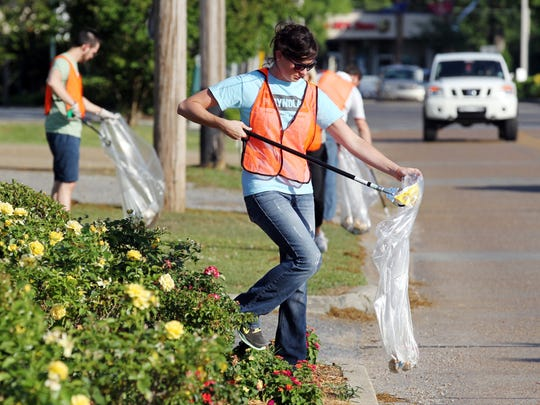 Bridget Tydor joins members of ReCover Acadiana, the 705 group, and other volunteers to clean up trash along Bertrand Drive in Lafayette Thursday, May 22, 2014.