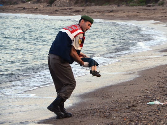A police officer carries the lifeless body of a migrant
