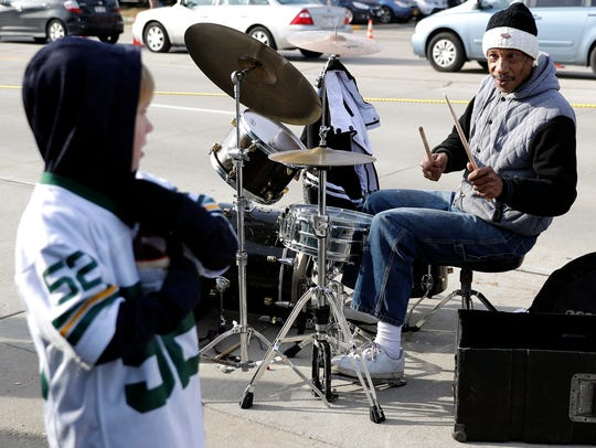 Keith Hudson offers a young Packers fan the chance to play his drum set while performing across the street from Lambeau Field on Dec. 3.