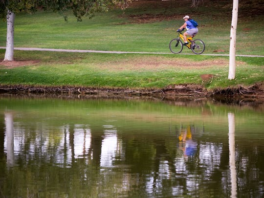A bicyclist rides on the pathway near the Indian Bend Wash greenbelt.