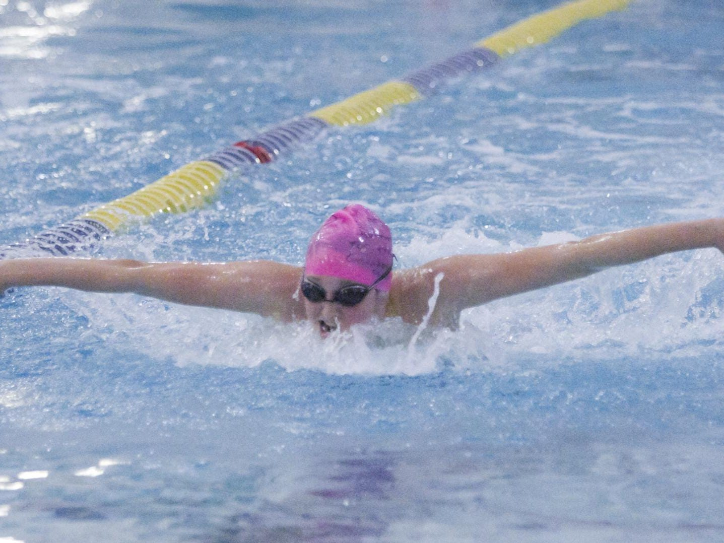 Maddie Mince of Hartland places second in the 100 yard butterfly, donning a pink swim cap with fellow Eagles for cancer awareness.