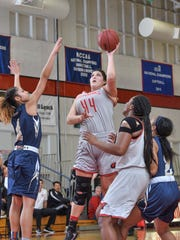 Simpson's Whitney Rodriguez, center, goes up for a