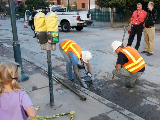 Denver Water Department workers toil outside the main gate of Coors Field in downtown Denver after a break in a major water main forced the cancellation of a baseball game between the Cincinnati Reds and the Colorado Rockies on Saturday, Aug. 16, 2014. The game will be played on Sunday as part of a split doubleheader. (AP Photo/David Zalubowski)