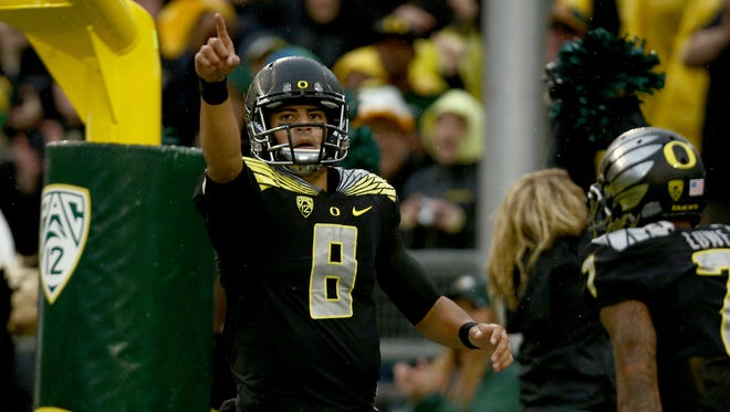 Oregon quarterback Marcus Mariota points to the crowd after scoring a touchdown during the first quarter against Stanford in Eugene. Mariota threw for two touchdowns and ran for two more in the 45-16 victory.