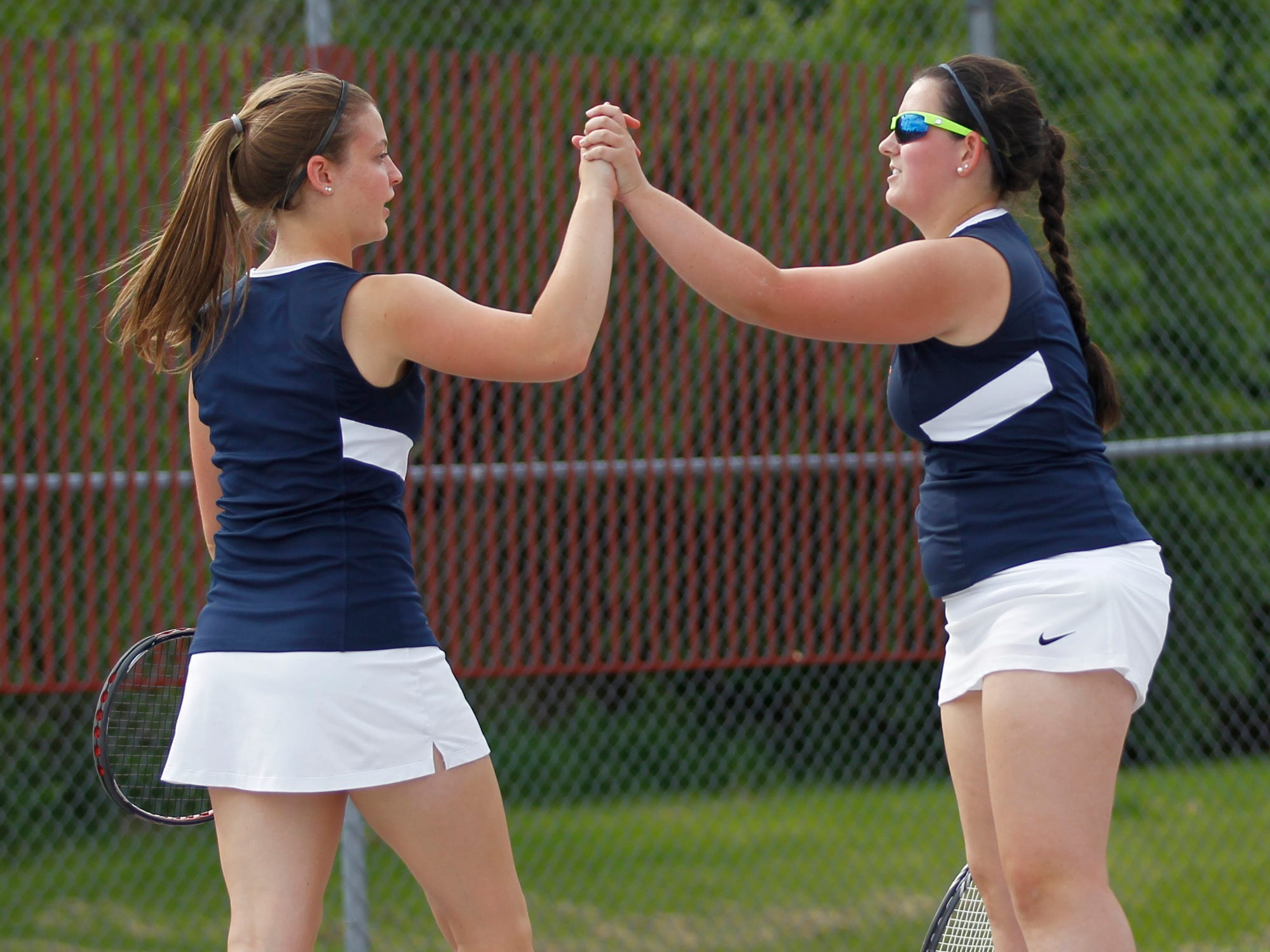 Harrison's Janie Zeh, left, and Hannah Eastman celebrate a point in their match at No. 2 doubles against Alyssa Tharp and Lizzi Cramer of Central Catholic during the West Lafayette girls tennis sectional Friday at Cumberland Elementary School. Eastman and Zeh won 6-0, 6-3.