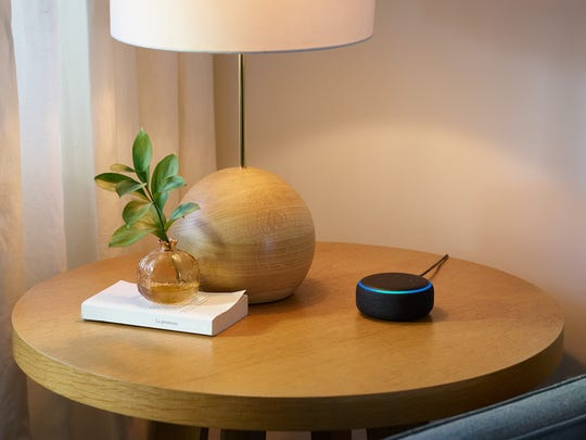 Amazon Echo Dot sitting on a table next to a lamp