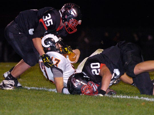 Pleasant Spartans defenders Kyle Galyk and Cade Lawrence take down Upper Sandusky receiver Kolin Holloway during first-half action in high school football Friday night, Oct. 17, 2014, at Pleasant High School.
