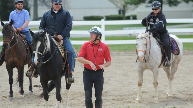 Sgt. Chris Laster gives instructions to Richmond Police Department Lt. Donnie Benedict during mounted patrol school at the Wayne County Fairgrounds.