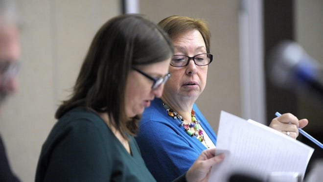 Democrats Jeannette L. Bradshaw, left, and Julie Maturak look over paperwork at a Board of State Canvassers meeting.