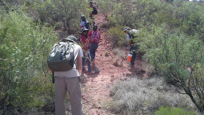 Volunteers clean up a segment of the El Camino Real de Tierra Adentro National Historic Trail leading to an interpretive site called the Yost Overlook, off Interstate 25 and Exit 32 past the Jornada Del Muerto Scenic Historical Marker (milepost 22.8).