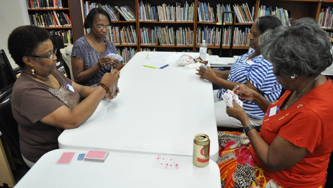 Vernell Howard (left), Ameil Washington (left middle), Esther Jones (right middle) and Juanita Scott (right) play a game of cards at the Rapides Parish Main Library.