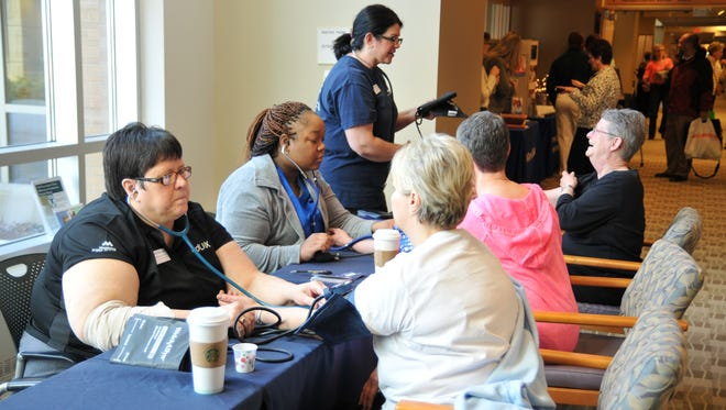 Attendees at last year's Women's Health 101 have their blood pressure taken.
