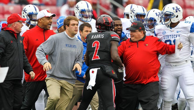 Louisville coach Bobby Petrino yells at far left as there were several heated moments between Louisville and Kentucky before the Governor's Cup game. Taunting occurred on both sides. Nov. 29, 2014 By Matt Stone/The C-J