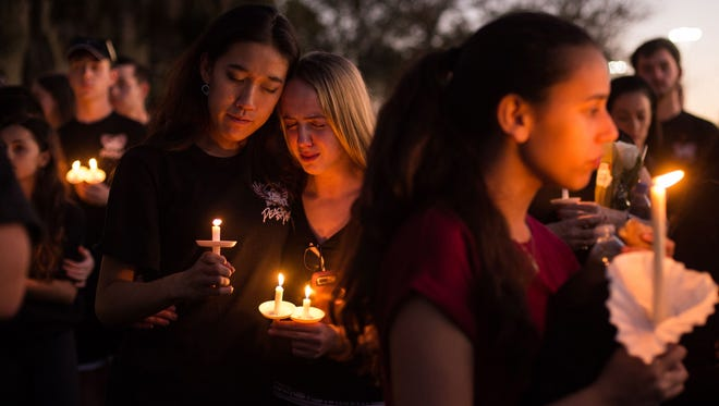 Members of the Stoneman Douglas Eagle Regiment mourn among thousands of other community members during a candlelight vigil at the Pine Trails Park amphitheater a day after a mass shooting at Marjory Stoneman Douglas High School in Parkland.