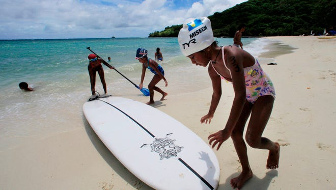 In this June 13, 2009 file photo, children play at a resort beach in Ngerkebesang, Palau. Lawmakers in the tiny Pacific island nation of Palau passed a law Thursday, Oct. 22, 2015 to make almost all its coastal waters a marine sanctuary in the latest move to expand ocean protections. A news release said Palau's president plans to sign the legislation next week. Friday is a national holiday in Palau.
