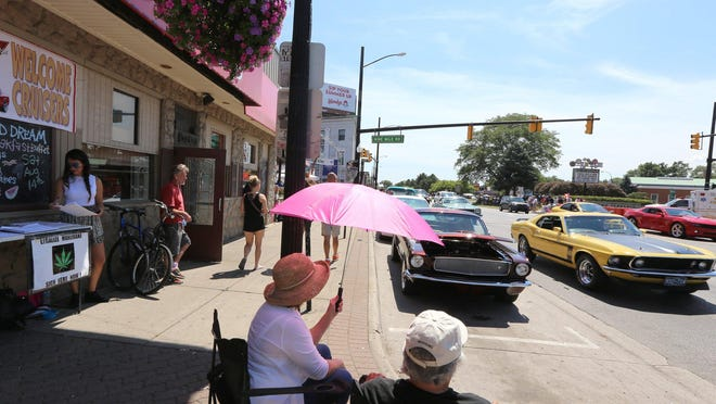 Charlotte Carron of Ferndale holds a pink umbrella as she sits with Rod Dotten of Madison Heights on Saturday in Ferndale. By itself, this year's Dream Cruise and the week leading up to cruise day had an economic impact on metro Detroit estimated at $75 million.