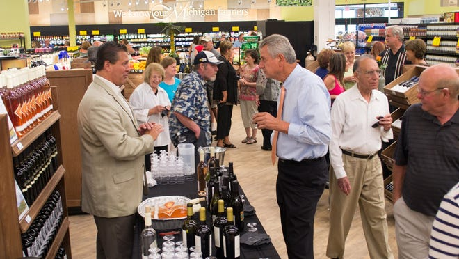 In this July 2013 photo, a vendor talks with Spiro Gagrica, right, a manager from SpartanNash at the Neiman's Family Market in Clarkston. Gagrica Spiro is a member of the team that designed the store, which officially opened to the public in July 2013.