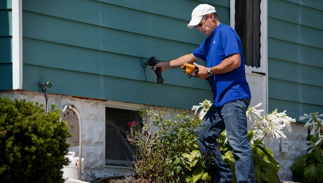 Water operator Wally Mencavage checks the water meter on the side of a home in St. Clair.