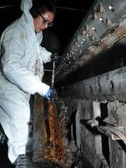 "A sailor removes ""lava rock"" insulation from a catapult"