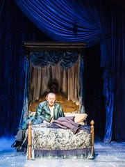 "William McNulty as Ebenezer Scrooge in his bed Actors Theatre of Louisville's updated production of ""A Christmas Carol."""