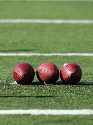 Three footballs lay on football field.