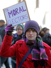 Cori Bishop of Egg Harbor City holds a sign outside