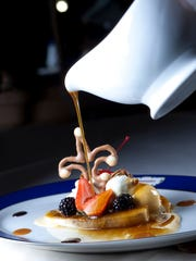 A Bananas Foster dish is topped with an edible fleur