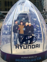 Fans pose for a photo in a snow globe last week at