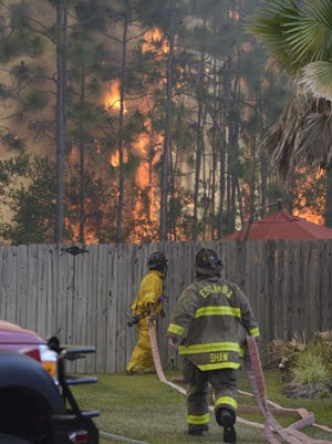 A large wildfire burns behind houses on Weatherstone Circle in Pensacola on May 7, 2018.