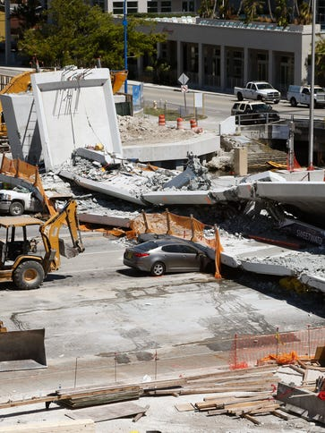 Crushed cars are shown under a section of a collapsed