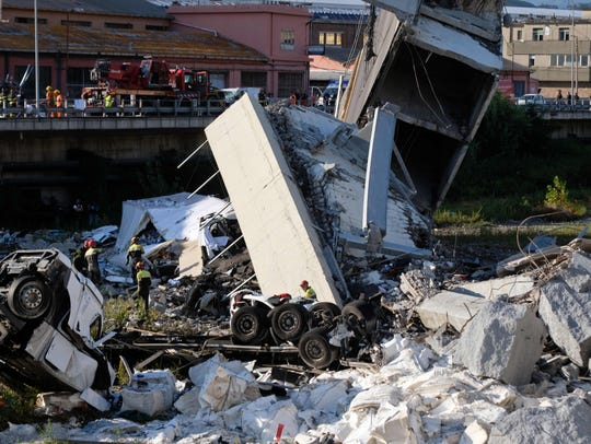 Rescuers inspect the rubble and wreckages by the Morandi