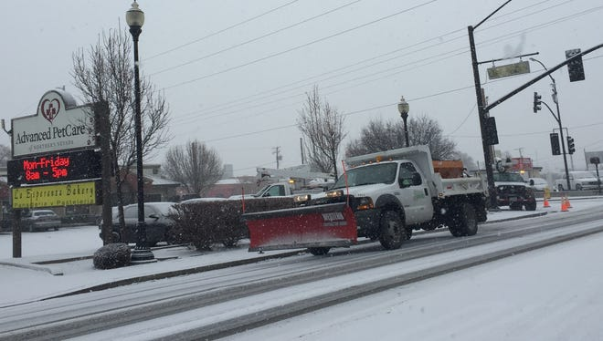 A snow plow passes utility workers working on the traffic signal at Sullivan Lane and Prater Way on Wednesday morning.
