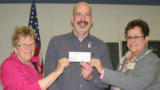 Marilyn Holder (left) and Winnie Decker present donation check to Fairview head librarian Philip McAndrew.