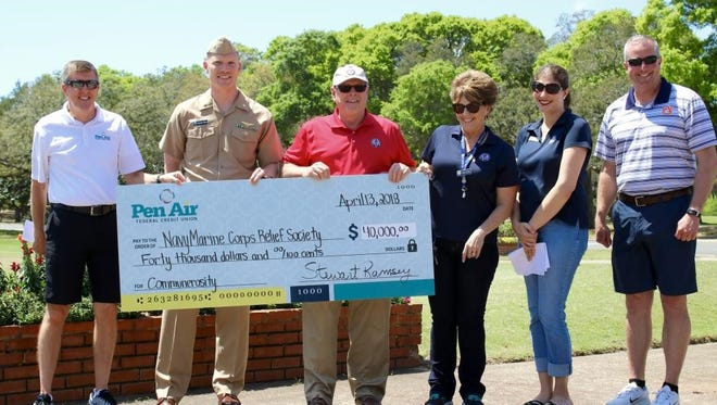 From left, Stu Ramsey, president and CEO of Pen Air Federal Credit Union; Lt. Cmdr. Timothy White; Mark Harden, director of the Navy-Marine Corps Relief Society; Amanda Shadden, relief services assistant; Angela Setering, volunteer at NMCRS; and Capt. Christopher Martin are pictured with a $40,000 check that was presented to the society Friday at the 18th Annual Friends of the Navy-Marine Corps Relief Society Charity Golf Tournament at the A.C. Read Golf Course.