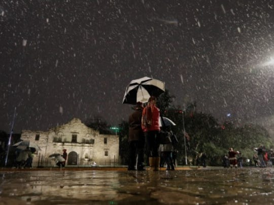 Visitors walk near the Alamo as snow falls in downtown