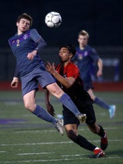 Norwalk freshman Spencer Taylor heads the ball in front