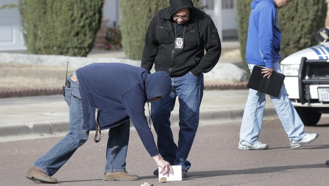Investigators look at evidence in the street in the 10300 block of Pasadena Circle in Northeast El Paso on Thursday afternoon.