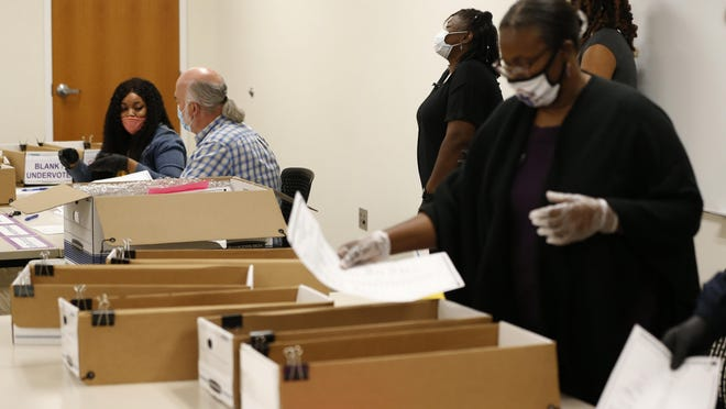 Poll workers recount ballots at the Clarke County Board of Elections Office in downtown Athens.