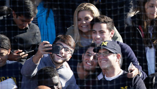 Michigan football coach Jim Harbaugh stops and takes selfies before President Barack Obama and Democratic nominee Hillary Clinton campaigns on the eve of Election Day at Ray L. Fisher Stadium in Ann Arbor on November 7, 2016.