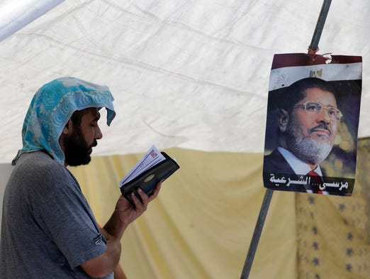 A supporter of ousted Egyptian president Mohammed Morsi reads the Quran on July 12 in Cairo's Nasr City district.