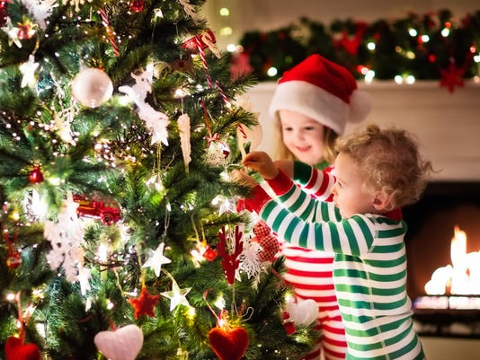 Kids decorating Christmas tree in beautiful living room