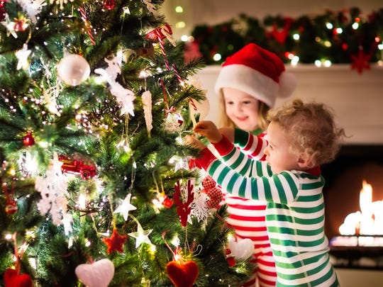 Happy little kids in matching pajamas decorating a Christmas tree.
