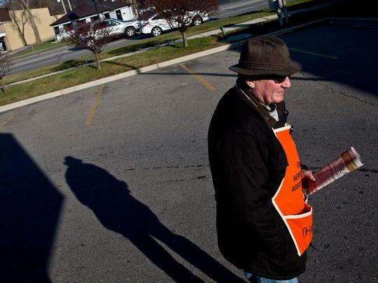 Volunteer Pat Mullins, of Port Huron, hawks newspapers