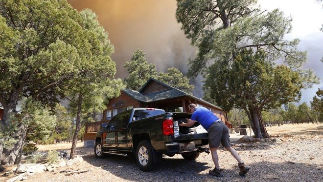 Chip Mandela evacuates his home as the Tinder Fire burns on the Mogolon Rim in the Coconino National Forest north of Payson, Ariz. April 29, 2018.