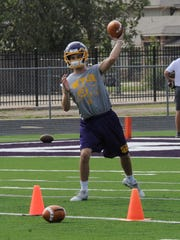 Wylie quarterback Sam King throws a pass during Monday's practice at Bulldog Stadium.