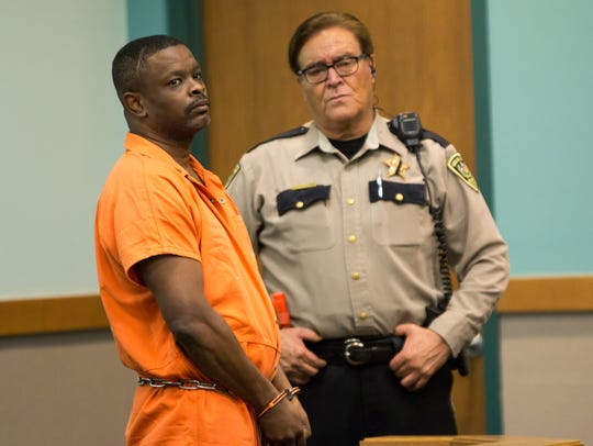 Tony Jones, left, stands during a scheduled arraignment