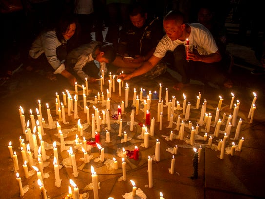 Indonesian residents light candles during a vigil for