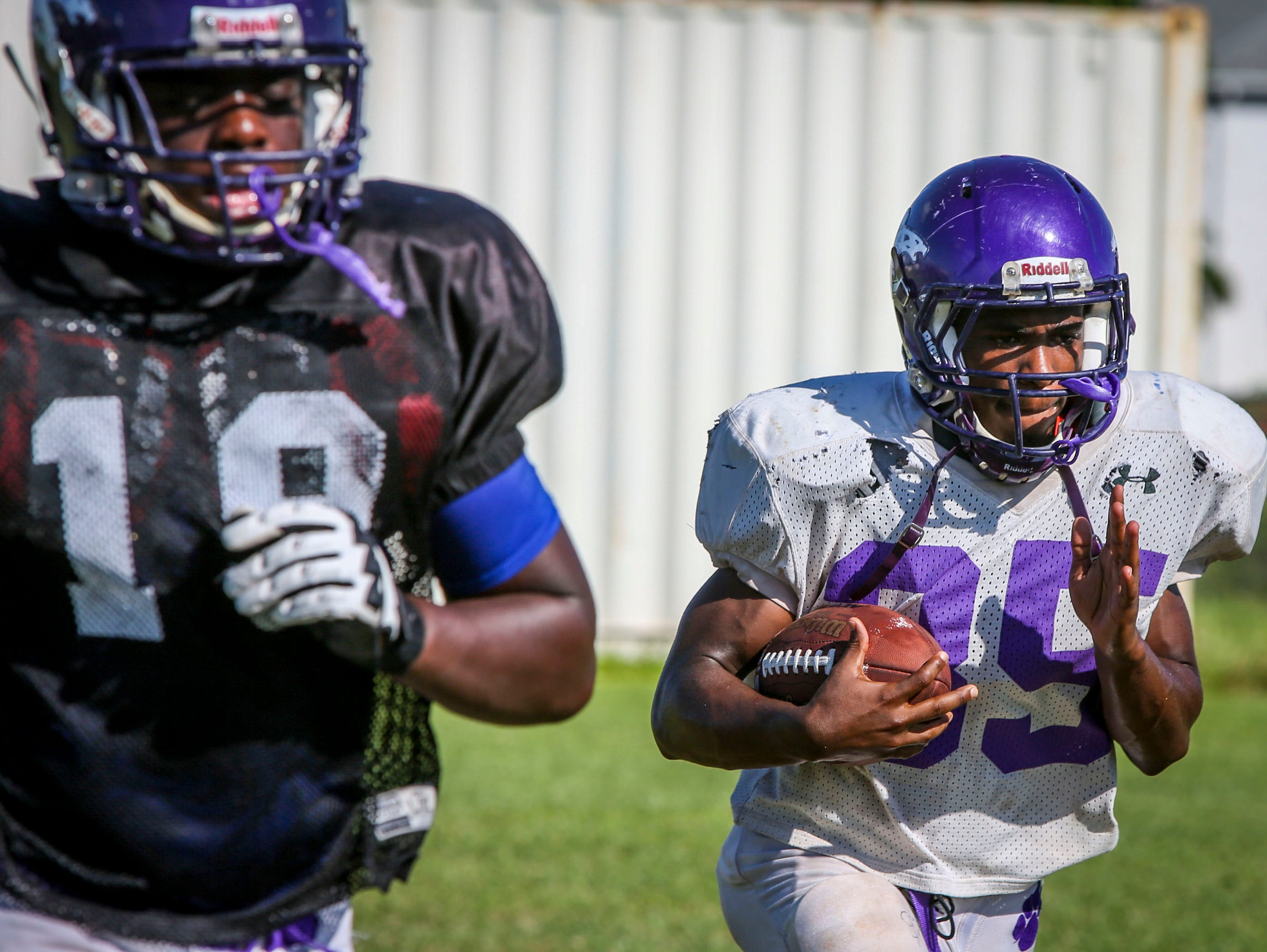 Cliff Moore, running back, for Cypress Lake High School carries the ball during football practice Wednesday afternoon.
