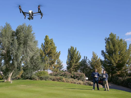 Ethan Kaminsky, left, and Dan Eslinger operate a drone while doing aerial videography at the Classic Club in Palm Desert, November 10, 2015.